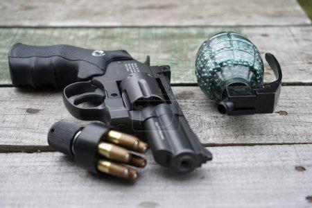 Photo pour Fusil à air comprimé, grenade décorative en plastique F1 avec cartouches pour fusils à air comprimé sur fond de bois. - image libre de droit
