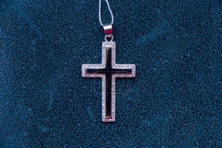 Srebrny Krzyż leży na zielonym kawałku skóry