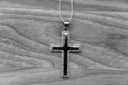 Srebrny Krzyż leży na drewnianej płycie-czarno-białe zdjęcie