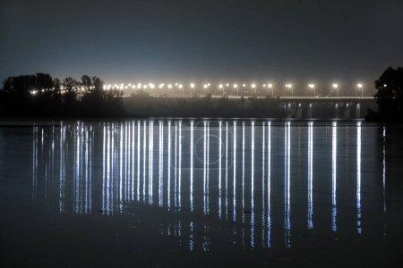 Photo pour Pont sur la rivière dniepr la nuit dans les lumières des lampadaires à longue exposition avec réflexion sur l'eau en ukraine - image libre de droit