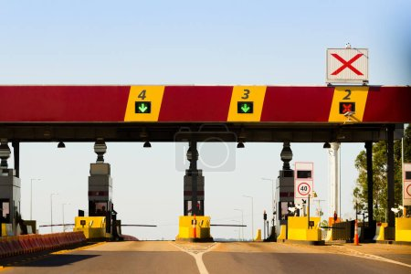 Toll payment point on a BR-163 highway in Mato Grosso do Sul. Red and yellow toll plaza with gates
