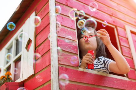 Boy blowing bubbles in a wooden playhouse