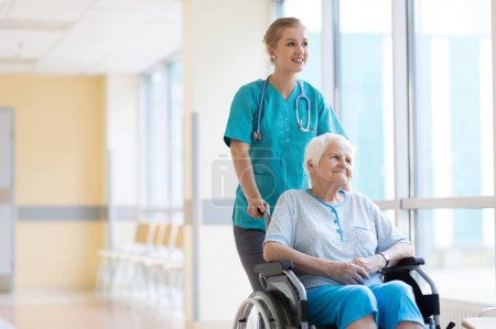 Photo for Senior woman in wheelchair with nurse in hospital - Royalty Free Image