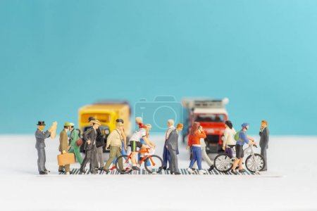 Photo for Miniature toys of crowd walking on zebra crossing with vehicles stopped concept. - Royalty Free Image