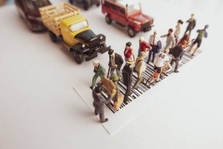 Photo for Vintage filter top view of miniature toys of crowd walking on zebra crossing with vehicles stopped concept. - Royalty Free Image
