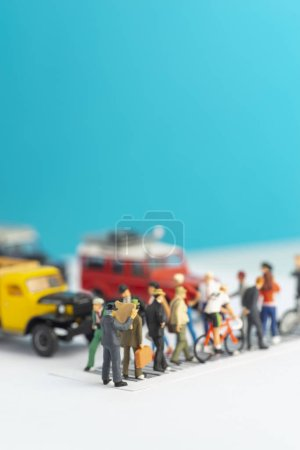 Photo for Miniature toys of a man reading newspaper, oblivious of his surrounding while crossing a street, reading habit concept. - Royalty Free Image