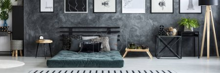 Simple posters hanging on texture wall in dark grey bedroom interior with fresh plant, mattress with cushions and small tables