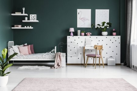 Posters on green wall in girl's bedroom interior with white bed and wooden pink chair at dressing table