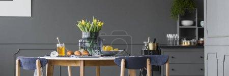 Photo pour Tulipes jaunes, croissants et thé sur table en bois gris, intérieur confortable de la salle à manger - image libre de droit