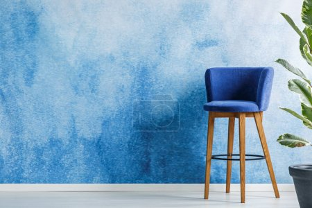 Photo for Bar stool standing in a living room interior next to a flower set on an empty wall painted with watercolor. Place your product - Royalty Free Image