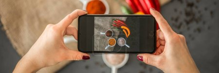 Top view of woman holding a phone and taking a photo of healthy food for her culinary blog