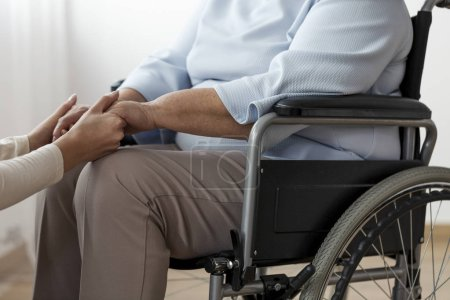 Close-up of a person supporting a paralyzed senior woman in a wheelchair