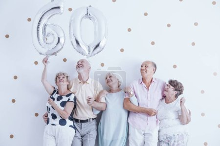 Grandmother and grandfather with silver balloons celebrating 60th birthday