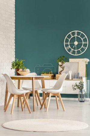Foto de Reloj moderno, mesa, sillas blancas y Alfombra redonda en un luminoso comedor interior - Imagen libre de derechos