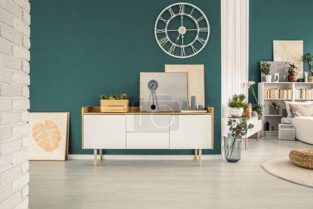 Photo pour Espace ouvert chambre à coucher intérieur avec vue frontale d'une armoire avec boîte en bois, peintures et horloge blanche - image libre de droit
