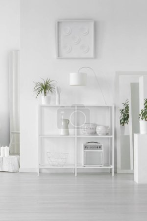 Photo for White metal rack with fresh plant, simple lamp and decor standing in bright room interior in Scandinavian style - Royalty Free Image