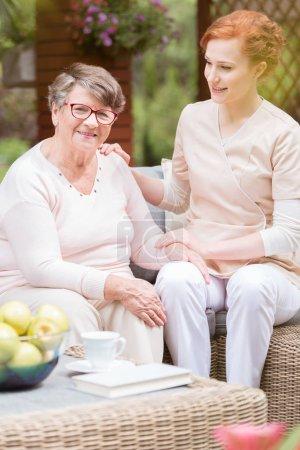 Photo pour Une soignante professionnelle soignante en uniforme met sa main sur l'épaule d'une femme âgée pendant le goûter sur le patio d'une maison de retraite. Fond flou . - image libre de droit