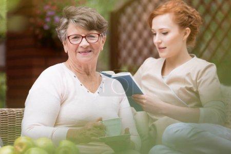 Photo pour Gros plan d'une heureuse aînée et d'une jeune infirmière qui lit un livre pendant ses loisirs sur le patio d'une garderie. Fond flou - image libre de droit