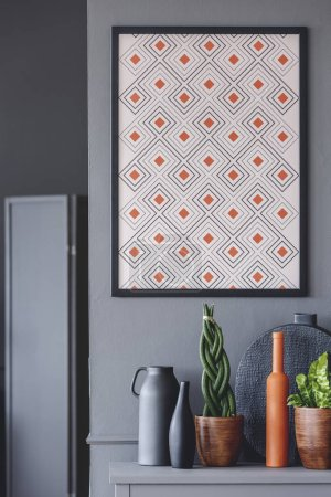 Photo for Geometrical poster with orange accents on the wall above plants and vases - Royalty Free Image