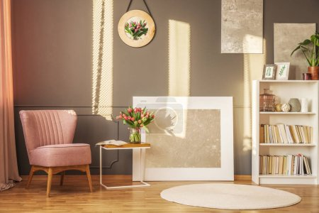 Photo for Pink armchair, flowers on a coffee table and grey painting in a sunny living room interior - Royalty Free Image