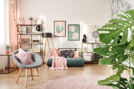 Photo pour Gros plan sur les feuilles, fauteuil gris avec un oreiller étoilé et matelas vert dans une chambre féminine intérieur - image libre de droit