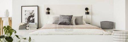 Photo pour Petites lampes placées sur la tête de lit blanche par le lit simple matelas avec oreillers dans l'intérieur de la chambre avec livres, horloge et affiche - image libre de droit