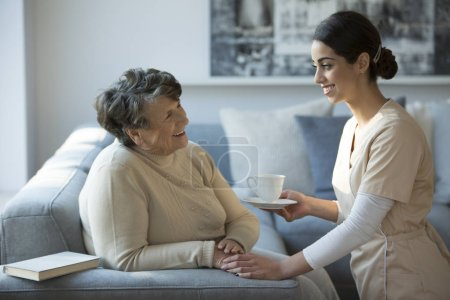 Nurse taking care of smiling grandmother while relaxing in the clinic