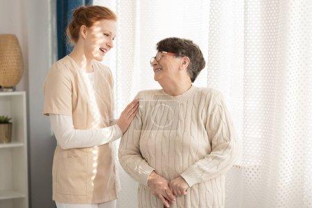 Photo pour Infirmière souriant en prenant soin d'une femme âgée heureuse dans une maison de retraite - image libre de droit