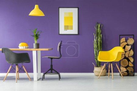 Photo pour Table à manger, chaises noires, affiche jaune, plantes et bois de chauffage dans un intérieur de salle à manger moderne - image libre de droit