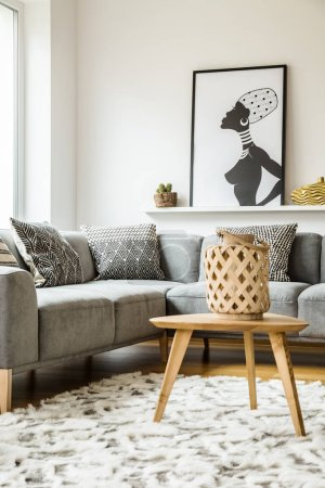 Photo for Wooden table on carpet next to grey corner couch in living room interior with poster. Real photo - Royalty Free Image