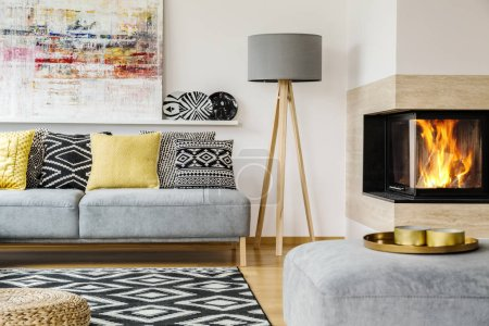Photo pour Lampe grise entre la cheminée et canapé avec des coussins à motifs en intérieur plat chaleureux avec la peinture. Vraie photo - image libre de droit