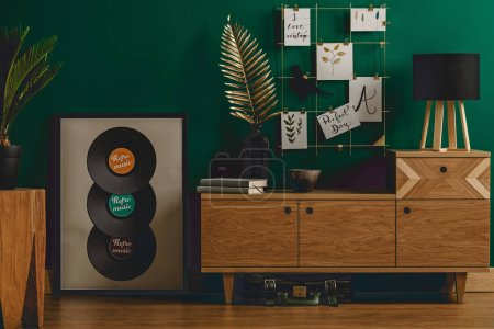Dark green vintage room interior with vinyls, cabinet, wooden floor, plant, lamp and decorations