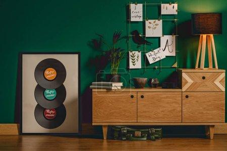 Dark, vintage living room interior with green walls, wooden floor, cupboard, vinyls and lamp concept