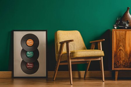 Yellow chair in vintage living room interior with green walls, wooden floor, cabinet and vinyls