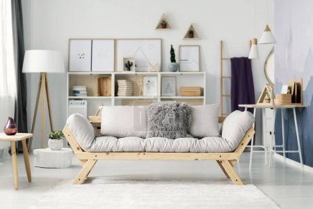 Beige sofa in bright, scandi living room interior with posters on a shelf between white lamp and ladder