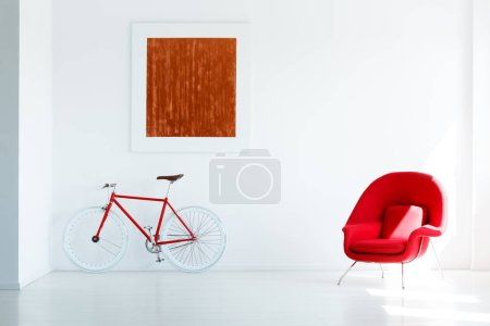 Red bike under painting in white modern loft interior with armchair. Real photo