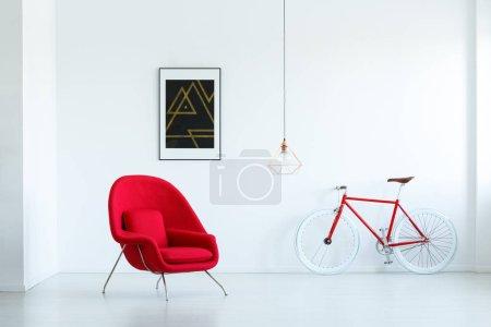 Photo pour Fauteuil rouge élégant dans un salon vide intérieur avec une peinture noire, lampe et vélo - image libre de droit