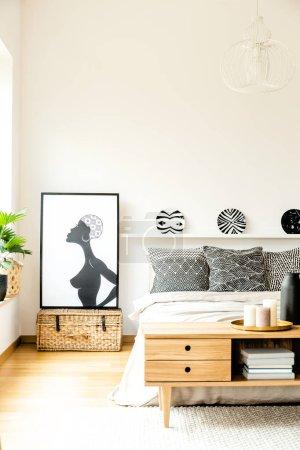 Photo pour Affiche africaine à côté du lit avec des oreillers à motifs sous les assiettes dans l'intérieur confortable moderne de la chambre - image libre de droit
