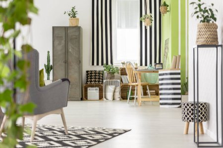 Striped drapes in modern apartment interior with metal cabinet and grey armchair on carpet. Real photo