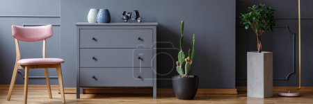 Photo for Powder pink chair standing by a grey cupboard with vases and motorcycle model in dark living room interior with potted plant and cactus - Royalty Free Image