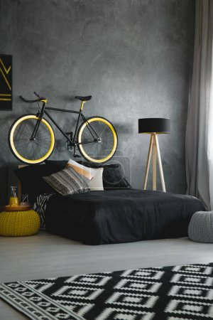 Photo for Bike above black bed against concrete wall in modern bedroom interior with patterned rug. Real photo - Royalty Free Image