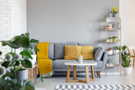 Photo for Orange pillows and blanket on grey couch in living room interior with wooden table. Real photo - Royalty Free Image