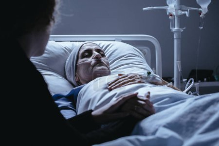 Dying senior woman with cancer in hospital bed with family support