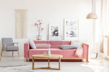 Patterned armchair and pink couch in feminist apartment interior with flowers and posters. Real photo