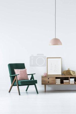 Photo pour Fauteuil vert avec oreiller rose à côté d'une armoire en bois dans le salon intérieur avec affiche - image libre de droit