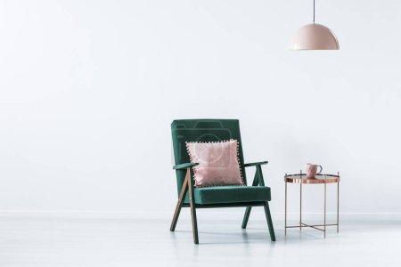 Photo pour Oreiller rose sur fauteuil vert à côté d'une table en cuivre à l'intérieur simple blanc avec espace de copie - image libre de droit