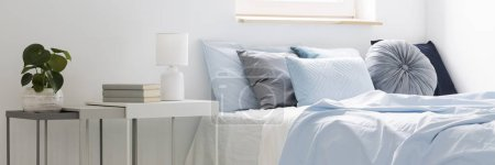 Photo for Real photo of a bed with blue bedding and cushions standing next to white tables with books, lamp and plant in bedroom interior - Royalty Free Image