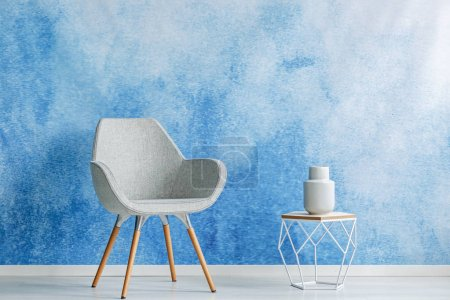 Copy space room interior with simple gray armchair and openwork side table with a dish on top against blue and white color ombre wall. Real photo.