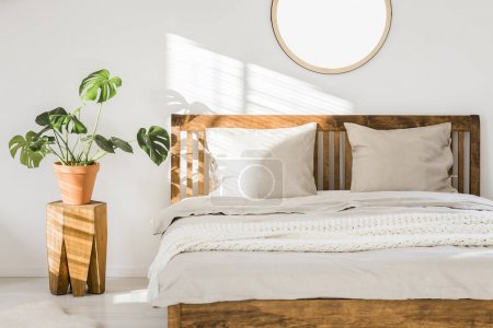 Photo for Wooden double bed with white pillows, sheets and knit blanket standing in bright bedroom interior with fresh plant on bedside table and round mirror on the wall - Royalty Free Image