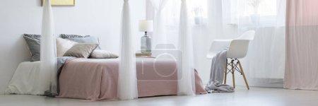 Photo pour Véritable photo d'un lit king-size dans un intérieur calme et équilibré à côté d'une chaise avec une couverture - image libre de droit